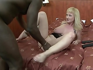 Blonde battle-axe Monik blows a long black dong and fucks it in bed