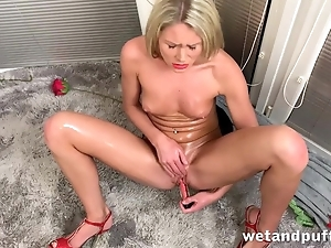 Slim blonde actively masturbates with red sexual intercourse toy