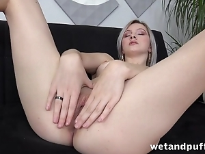 Platinum blonde seductively undresses on the couch