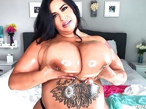 Hot BBW oils her immense boobs and plays not far from them